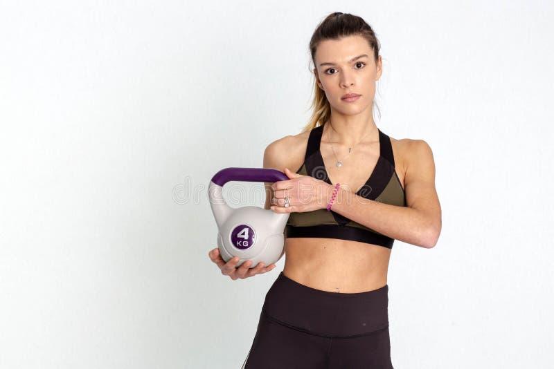 La mujer de la aptitud hace el oscilación del kettlebell Entrenamiento de CrossFit En el fondo blanco - Imagen fotos de archivo
