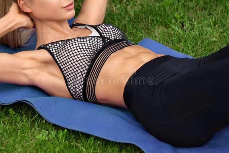 La mujer de la aptitud que el hacer se sienta sube, entrenamiento al aire libre Ejercicio atlético de la muchacha abdominal imagen de archivo