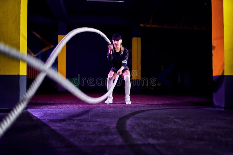 La mujer de la aptitud que usa el entrenamiento ropes para el ejercicio en el gimnasio El atleta que se resuelve con batalla rope fotos de archivo