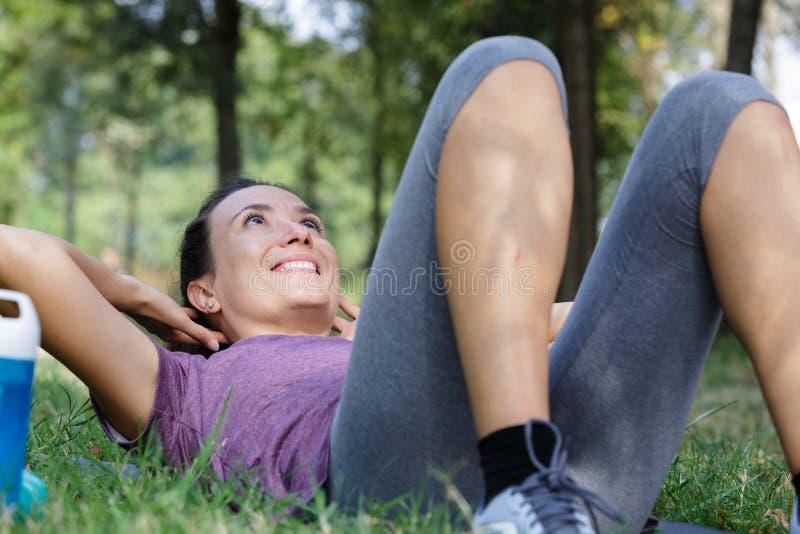 la mujer de la aptitud de Sentar-UPS que hace el ABS de la base del entrenamiento del situps ejercita afuera imagen de archivo
