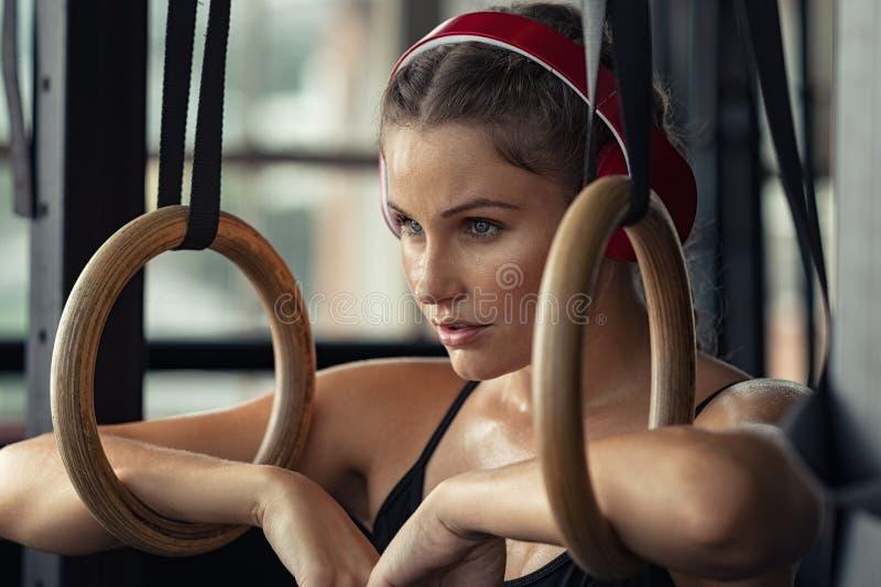 La mujer de la aptitud tiene una rotura en el gimnasio imagenes de archivo