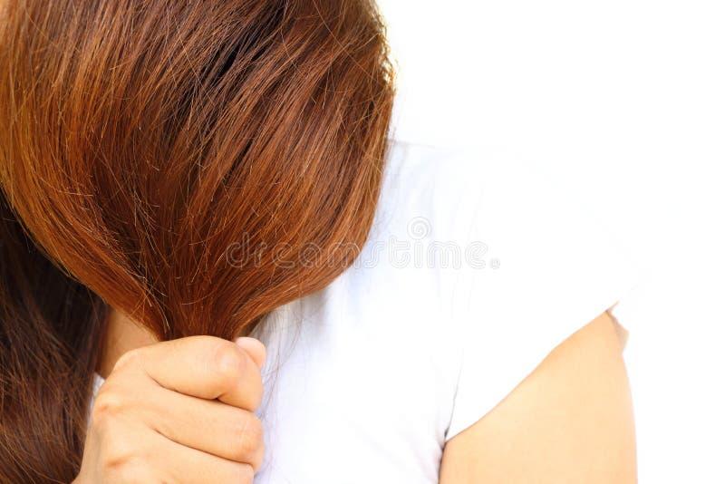 La mujer de Asia lleva la camisa blanca que se sostiene los pelos largos que hacen los tratamientos del color que razonan quizá h fotografía de archivo libre de regalías