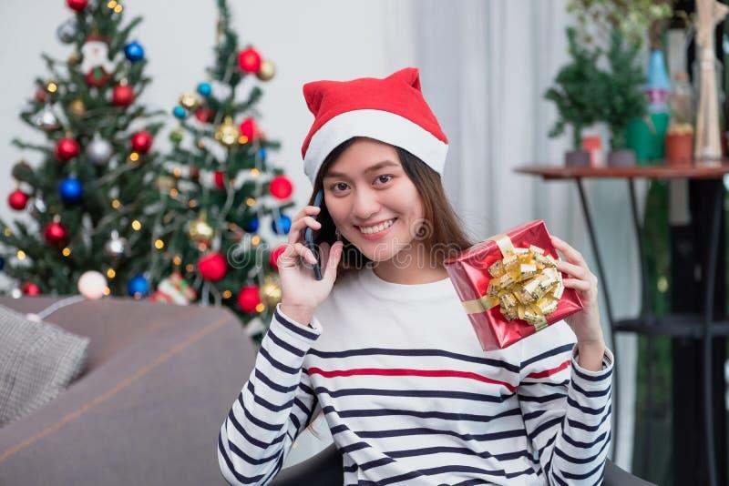 La mujer de Asia lleva el sombrero de santa y sostener la caja de regalo y utiliza charla móvil con el amigo y sentarse en el sof fotos de archivo libres de regalías