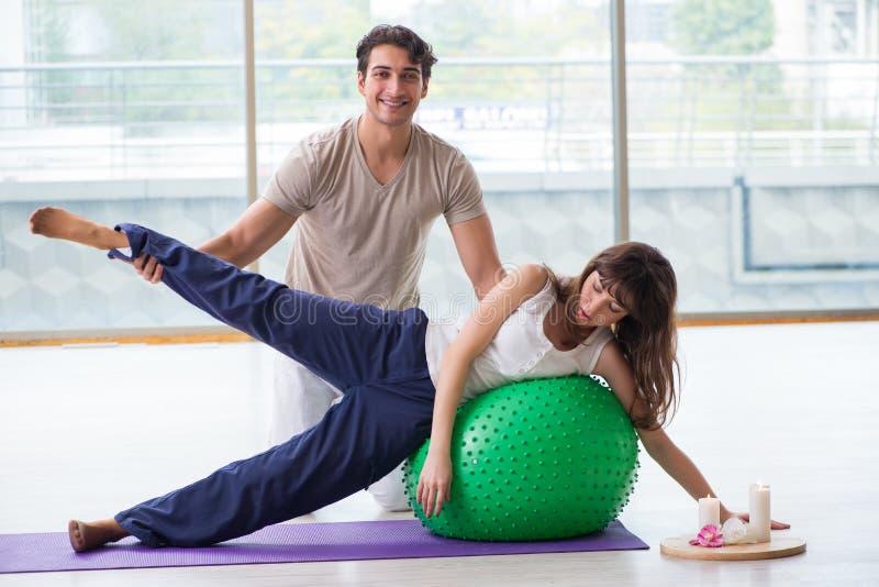 La mujer de ayuda del coche personal en gimnasio con la bola de la estabilidad imagen de archivo