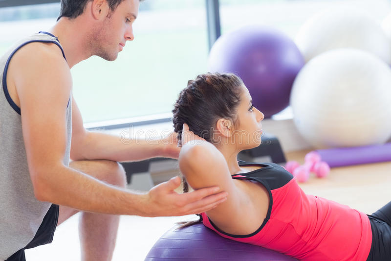La mujer de ayuda del instructor masculino hace crujidos en bola de la aptitud en el gimnasio foto de archivo libre de regalías