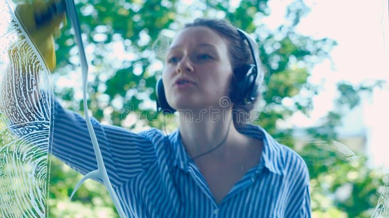 La mujer de baile joven en auriculares funciona con el enjugador en ventana fotos de archivo libres de regalías