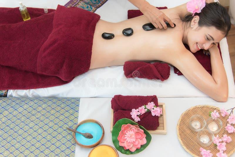 La mujer de la belleza de Asia que se acuesta en cama del masaje con las piedras calientes tradicionales a lo largo de la espina  imagen de archivo libre de regalías