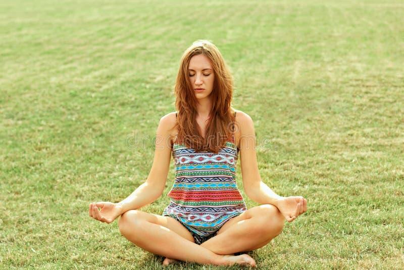 La mujer de la belleza practica yoga y medita en la posición de loto en el parque meditaci?n Forma de vida activa Conce sano y de foto de archivo