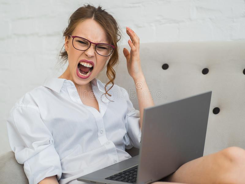La mujer de carrera agresiva trabaja en casa Mujer de griterío y frustrada con el ordenador portátil fotografía de archivo