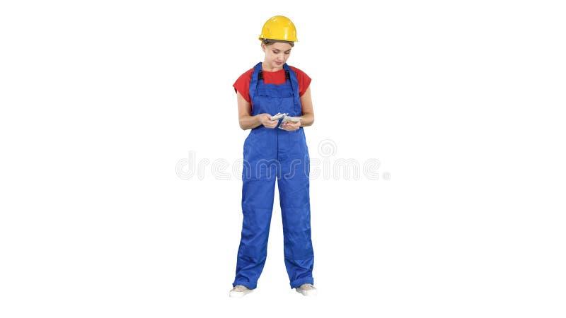 La mujer de la construcci?n cuenta el dinero y feliz despu?s de que el trabajo se haga en el fondo blanco fotos de archivo libres de regalías