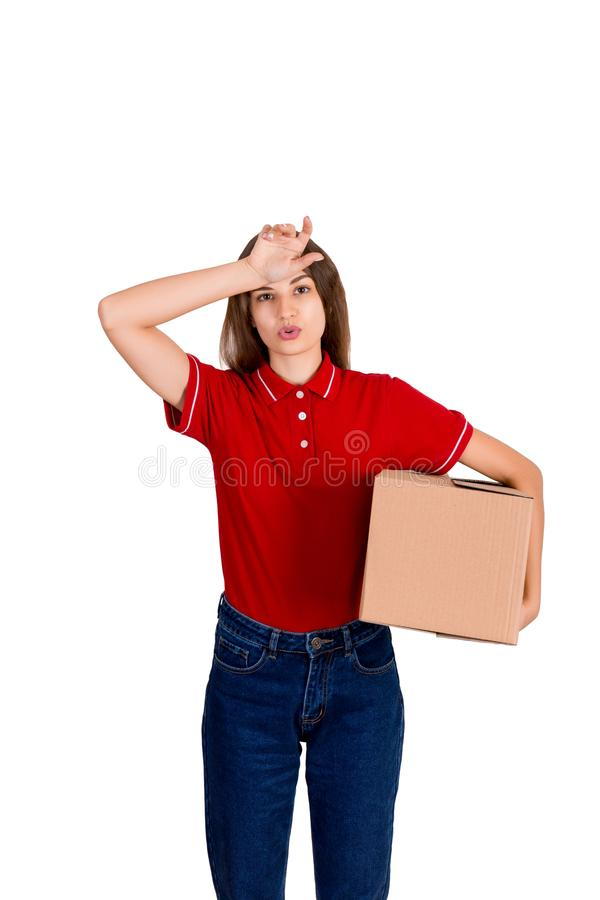 La mujer de la entrega siente cansada después de entregar un paquete pesado aislado en el fondo blanco fotografía de archivo libre de regalías