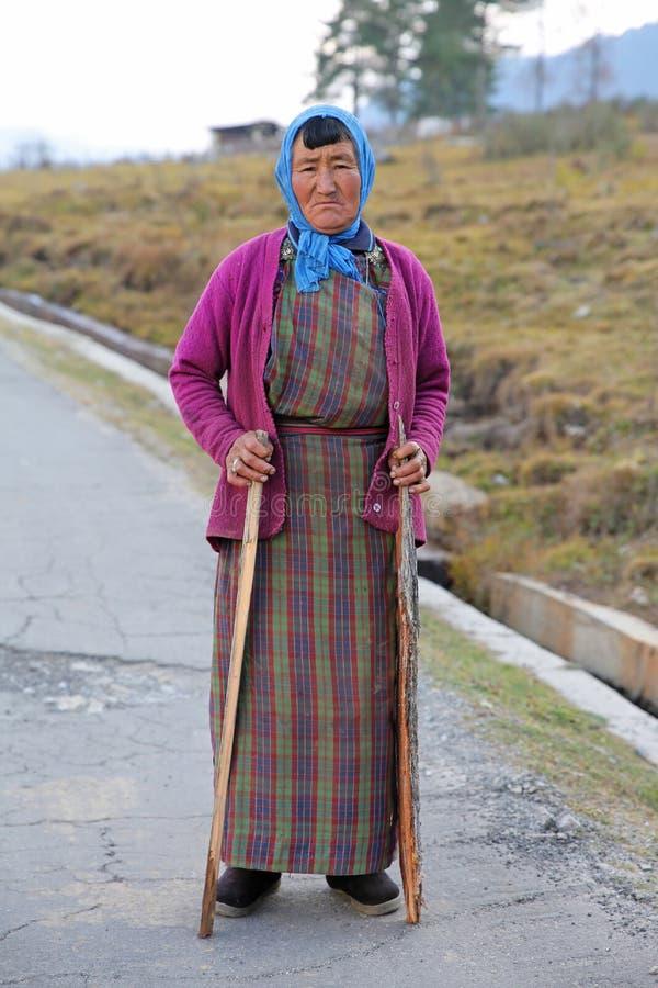 La mujer de la granja se detiene brevemente con los bastones en Bhután, visión vertical foto de archivo