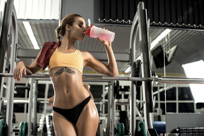 La mujer de la aptitud cansó en la nutrición juguetona de la bebida del gimnasio de la coctelera fotos de archivo libres de regalías