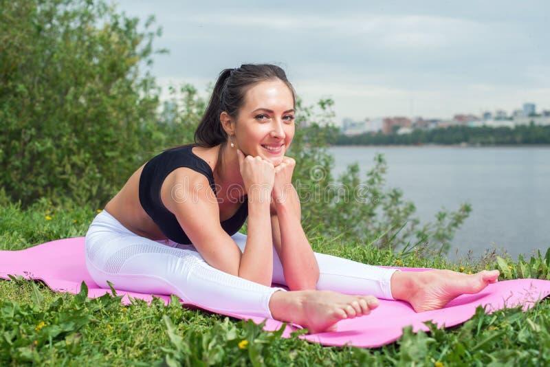 La mujer de la aptitud que estira detrás, pierna del tendón de la corva muscles la curva delantera asentada imagenes de archivo