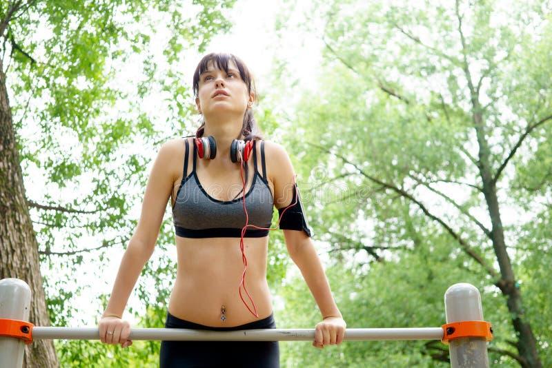 La mujer de la aptitud tiró en barra y los ejercicios el hacer en parque fotografía de archivo