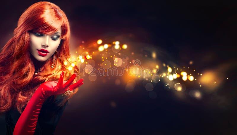 La mujer de la belleza con magia de oro chispea en su mano foto de archivo libre de regalías