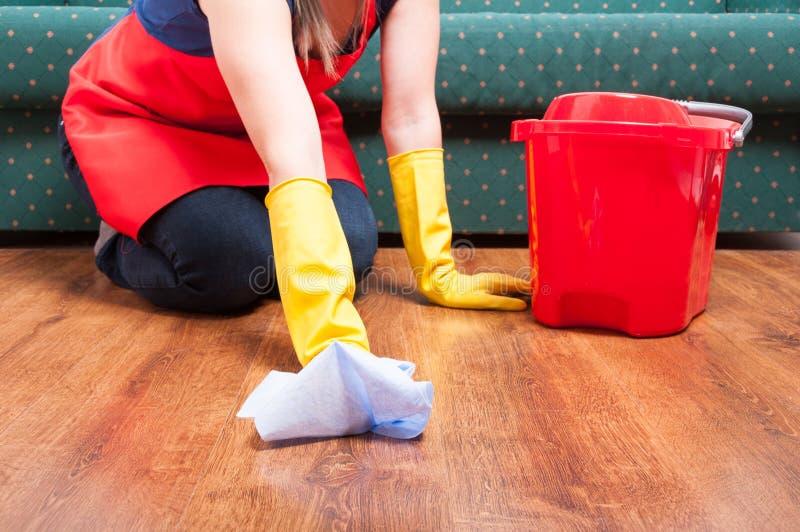 La mujer de la criada sienta y limpia el piso imagen de archivo