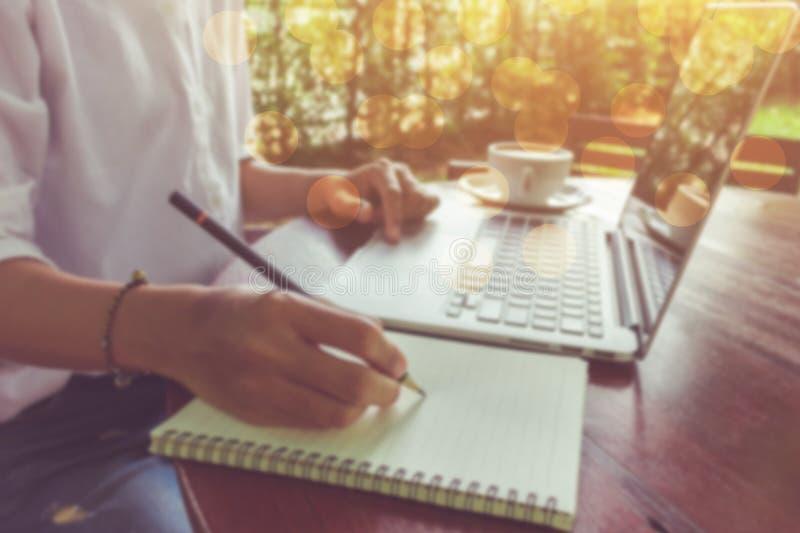 La mujer de la falta de definición escribe en el cuaderno y utiliza tono del vintage del ordenador portátil con el bokeh foto de archivo