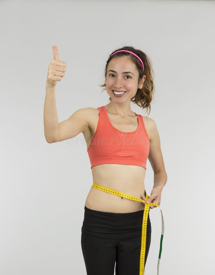 La mujer de la pérdida de peso manosea con los dedos para arriba imágenes de archivo libres de regalías