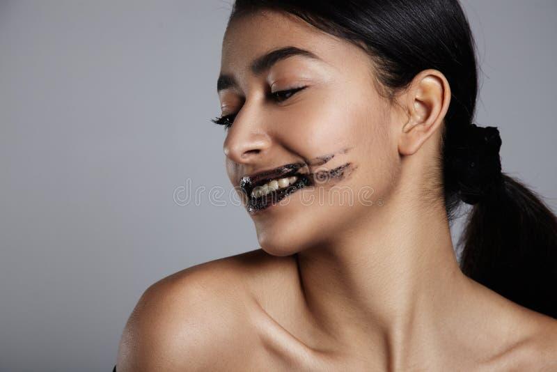 La mujer de la raza mixta de la belleza con un labio friega el tratamiento encendido imágenes de archivo libres de regalías