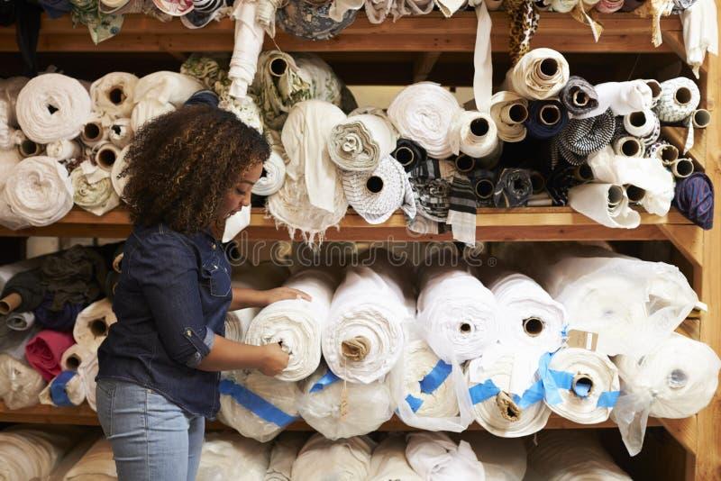 La mujer de la raza mixta selecciona la tela en un estudio del diseño de la ropa imágenes de archivo libres de regalías