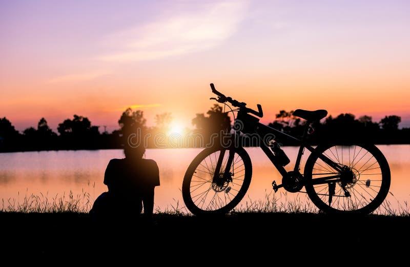 La mujer de la silueta se sienta cerca de la bicicleta en puesta del sol imagenes de archivo