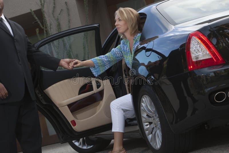 La mujer de las ayudas del chófer consigue abajo del coche fotografía de archivo