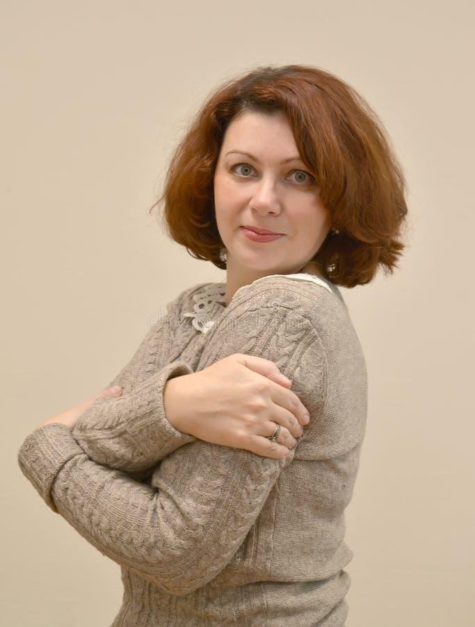 La mujer de los años medios se abraza Un retrato en un fondo ligero imagenes de archivo