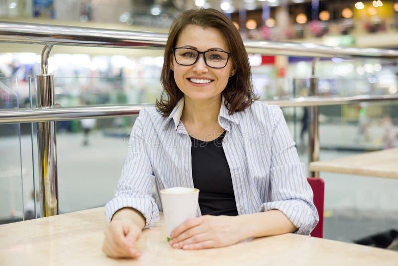 La mujer de mediana edad en una tabla con la taza de café mira la cámara que sonríe, centro de entretenimiento de las compras del imagen de archivo