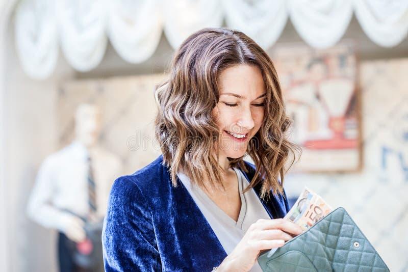 La mujer de mediana edad hermosa está contando billetes de banco en su cartera imágenes de archivo libres de regalías