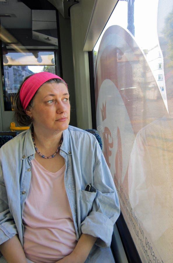 La mujer de mediana edad mira seriamente fuera de la ventana en una tranvía alemana imágenes de archivo libres de regalías