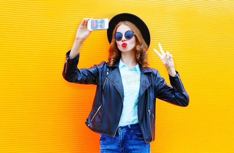 La mujer de la moda está tomando una imagen en un smartphone en chaqueta negra de la roca foto de archivo libre de regalías