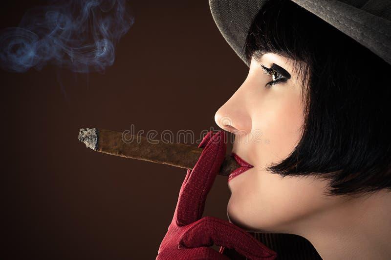 La mujer de moda fuma un cigarro imágenes de archivo libres de regalías