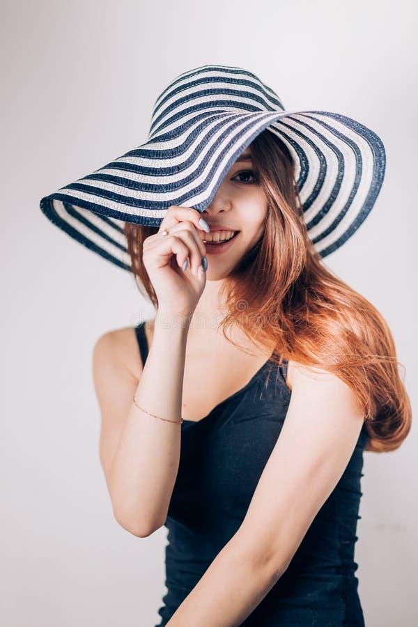 La mujer de moda hermosa en un sombrero mira sonriente, imagen de archivo libre de regalías