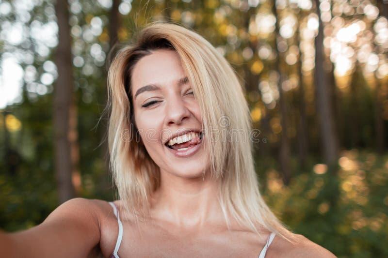 La mujer de moda joven feliz hermosa en un vestido rosado muestra la lengua y hace el selfie en el bosque en un día soleado brill foto de archivo