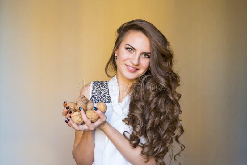 La mujer de moda mantiene las nueces sus manos fotos de archivo