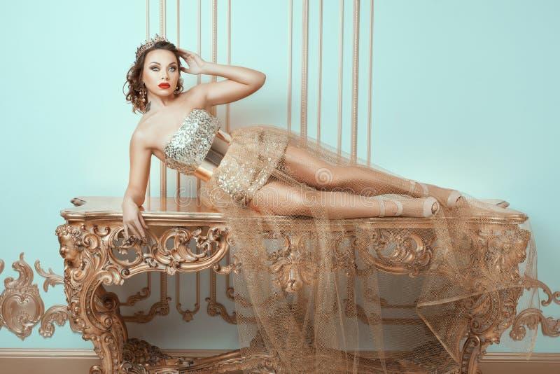 La mujer de moda miente en una tabla antigua costosa fotografía de archivo libre de regalías