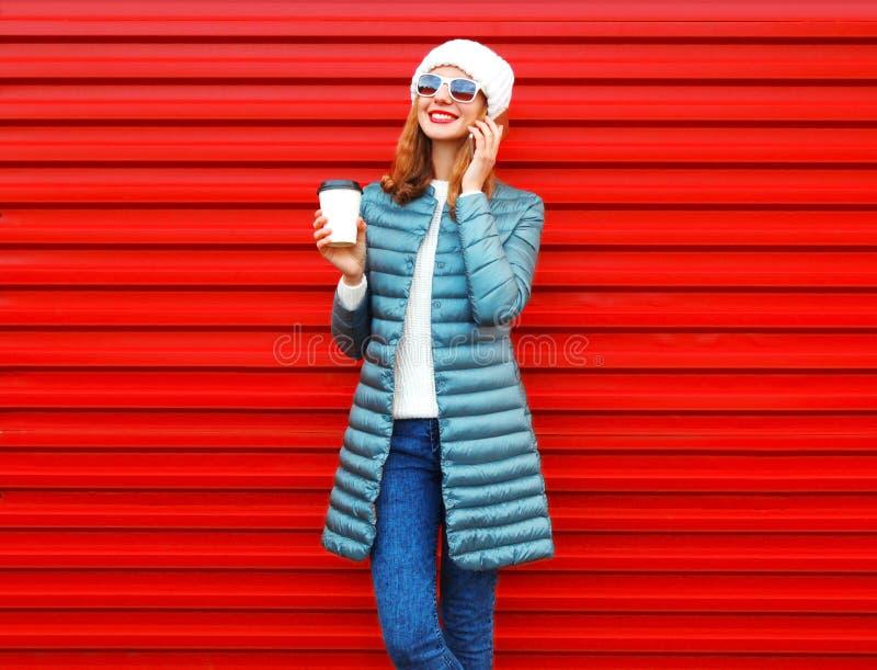 La mujer de la moda que sonríe negociaciones sobre un smartphone sostiene la taza de café imagen de archivo