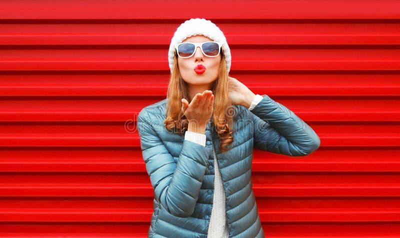 La mujer de la moda que sopla los labios rojos envía un beso del aire en fondo foto de archivo libre de regalías