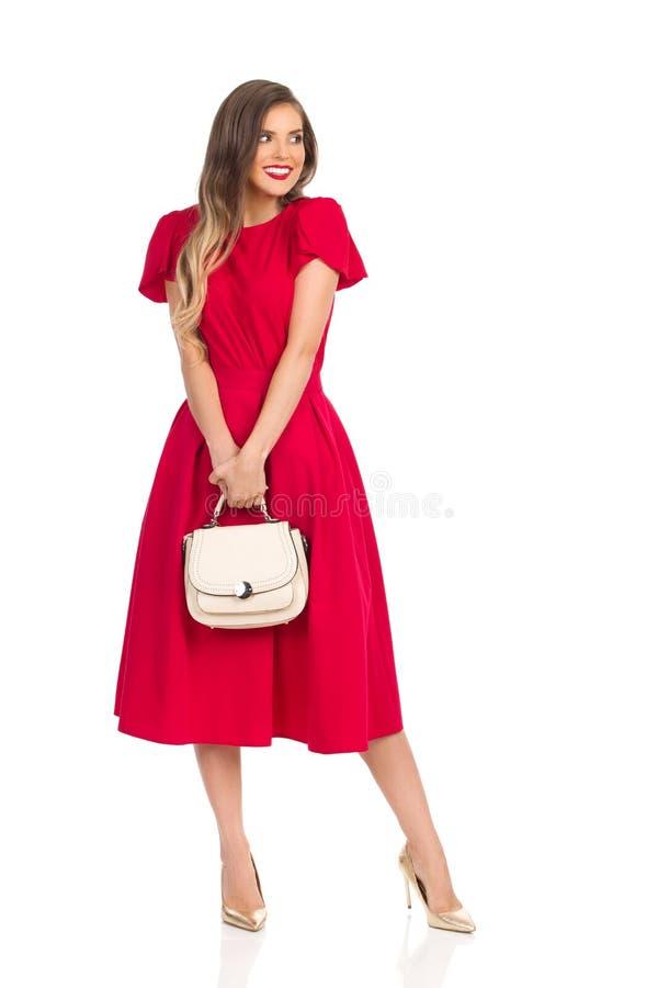 La mujer de moda tímida en vestido rojo, tacones altos del oro y monedero beige está mirando lejos y sonrisa foto de archivo