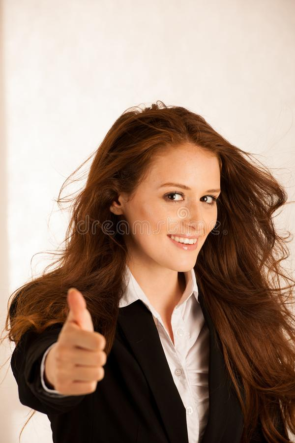 La mujer de negocios acertada atractiva muestra el tumb para arriba como gesto f imagenes de archivo