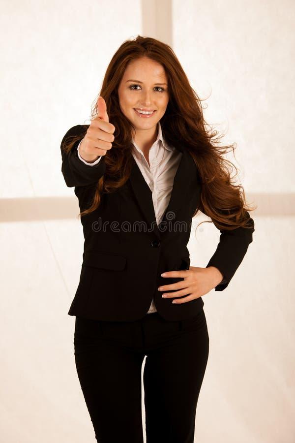 La mujer de negocios acertada atractiva muestra el tumb para arriba como gesto f fotografía de archivo