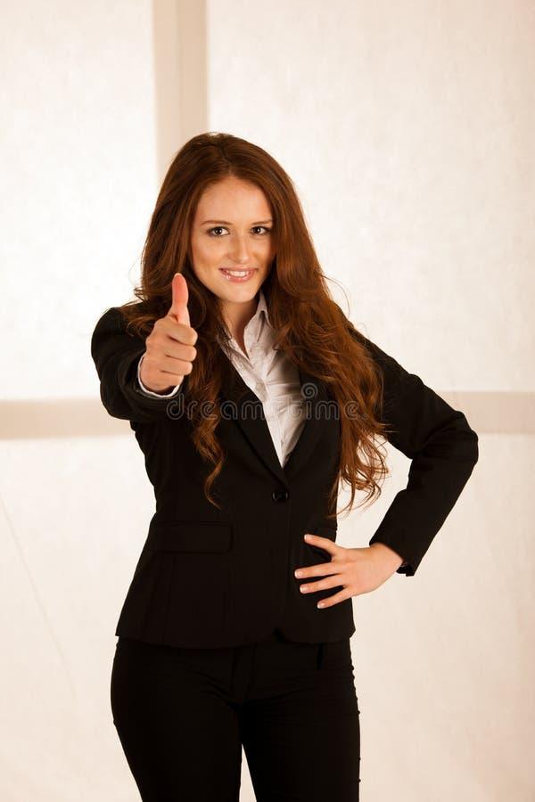 La mujer de negocios acertada atractiva muestra el tumb para arriba como gesto f imagen de archivo