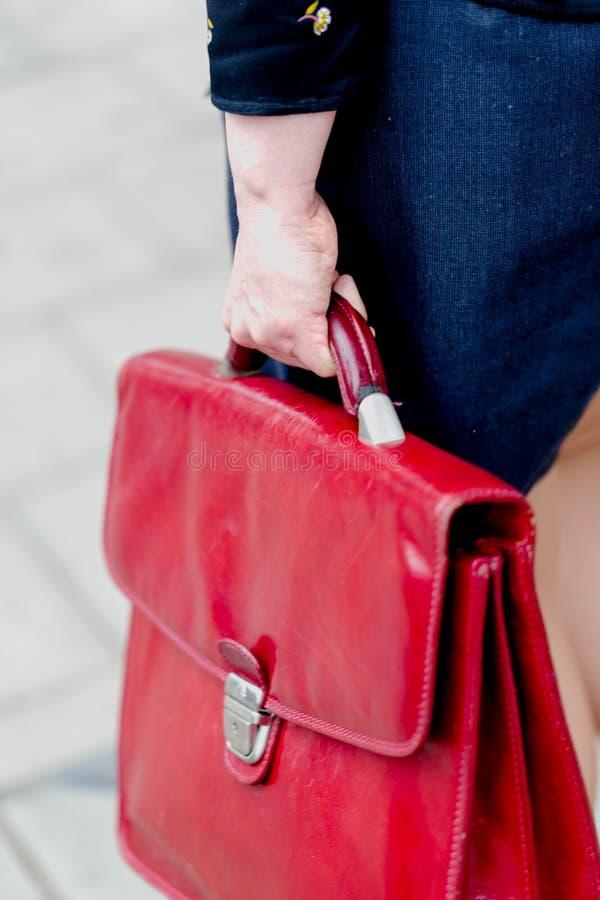 La mujer de negocios adulta joven sostiene la cartera de cuero roja imágenes de archivo libres de regalías