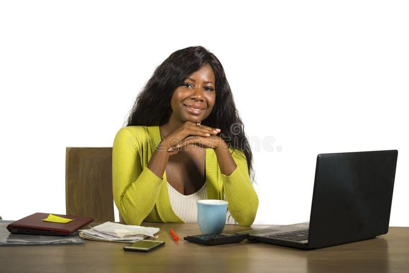 La mujer de negocios afroamericana negra feliz y atractiva joven que sonríe trabajo alegre y confiado en el escritorio del ordena foto de archivo