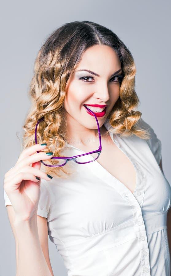 La mujer de negocios alegre sonriente sostiene los vidrios disponibles foto de archivo