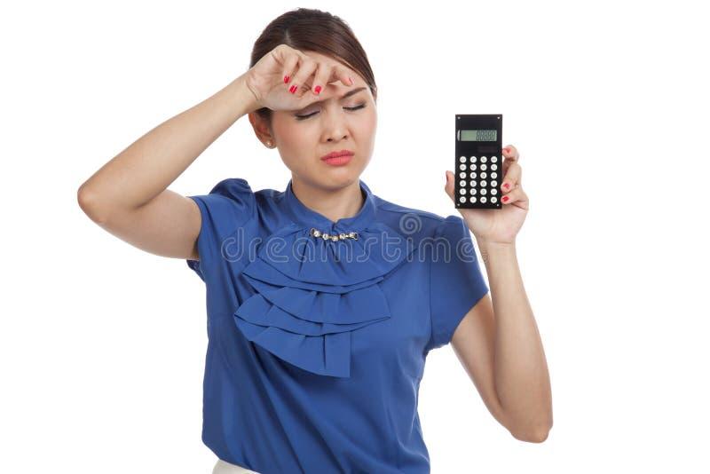 La mujer de negocios asiática consiguió dolor de cabeza con la calculadora imagen de archivo libre de regalías