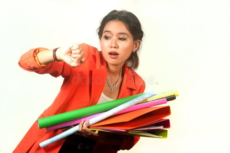 La mujer de negocios que sostiene carpetas y los papeles está precipitado. fotografía de archivo libre de regalías