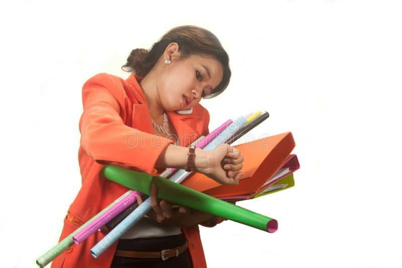 La mujer de negocios que sostiene carpetas y los papeles está precipitado. imagen de archivo libre de regalías