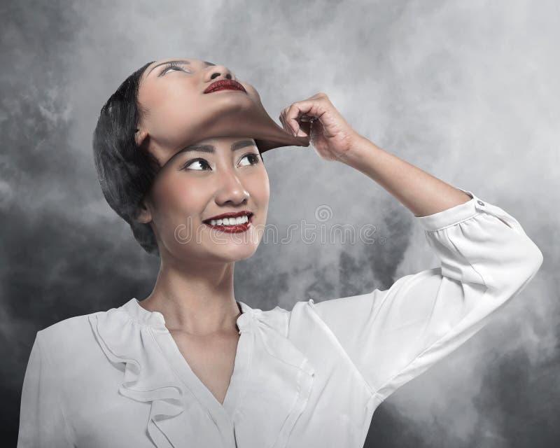 La mujer de negocios asiática quita su otra mascarilla imágenes de archivo libres de regalías